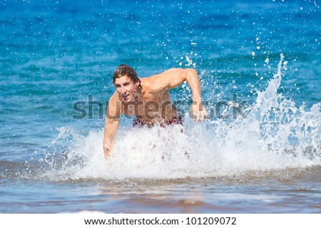 Physically fit man running on Beach in Hawaii