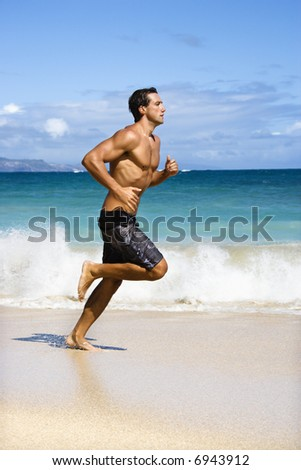 Physically fit man running on Maui, Hawaii beach.