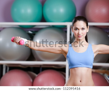 Physically strong woman training with dumbbells in gym - stock photo
