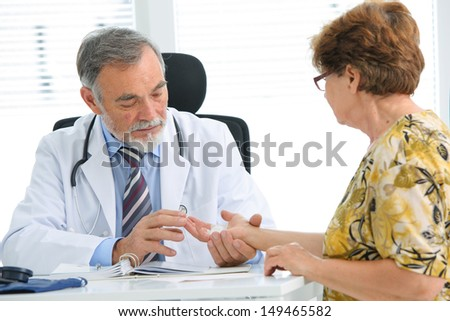 Physician examines the injured hand of the patient - stock photo