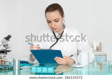 Physician in white coat checks patients records - stock photo