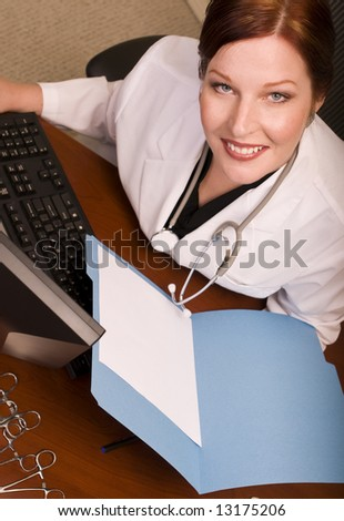 Physician or other medical professional reviewing file at her desk. Blank file page for your copy. - stock photo