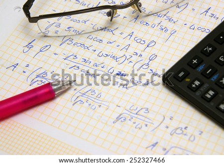 Physics and math exam, study set (hand writing notes, glasses, pencil and calculator - stock photo