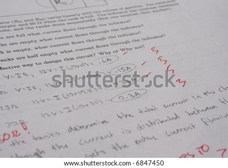 Physics exam with red pen markings