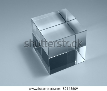 physics theme with studio photography of a solid glass cube in light back, blue toned - stock photo