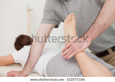 Physiotherapist bending the leg of his peaceful patient in a room