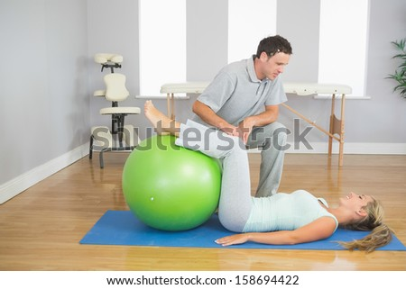 Physiotherapist checking patient doing exercise with exercise ball in bright room - stock photo