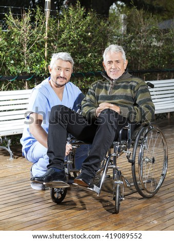 Physiotherapist Crouching By Senior Man In Wheelchair At Lawn - stock photo