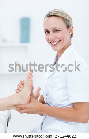Physiotherapist doing foot massage in medical office - stock photo