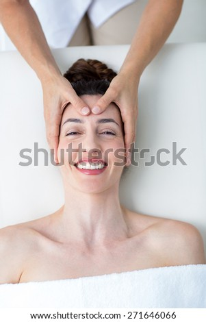 Physiotherapist doing head massage in medical office - stock photo