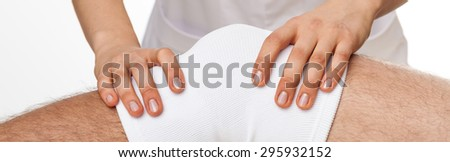 Physiotherapist doing kneecap mobilisation - isolated, white background - stock photo