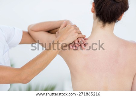 Physiotherapist doing shoulder massage in medical office