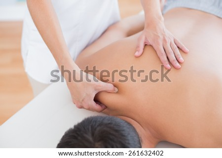 Physiotherapist doing shoulder massage to her patient in medical office - stock photo