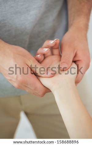 Physiotherapist examining the hand of a patient in bright office