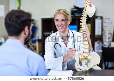 Physiotherapist explaining spine model to patient in clinic - stock photo