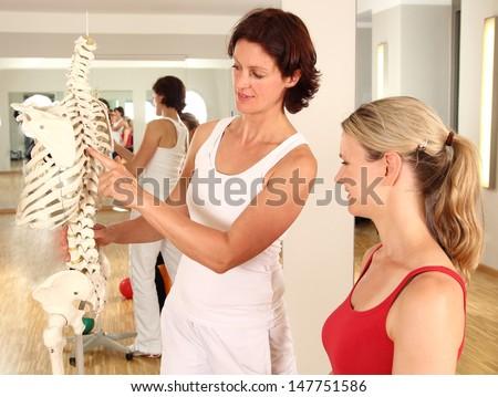 Physiotherapist explaining the spine - stock photo