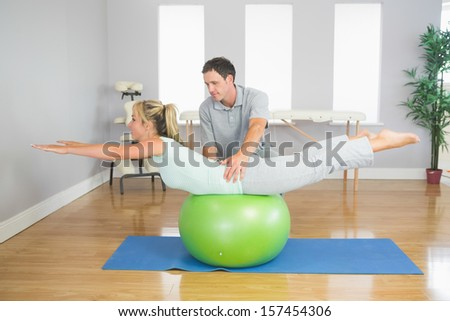 Physiotherapist helping patient doing exercise with exercise ball in bright room - stock photo