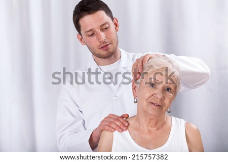 Physiotherapist helping patient with pain of neck - stock photo