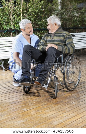 Physiotherapist Looking At Disabled Senior Man In Wheelchair - stock photo