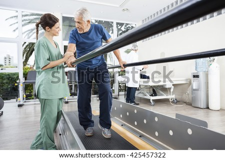 Physiotherapist Looking At Senior Patient Walking Between Parall - stock photo