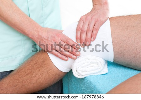 Physiotherapist making a massage of injured patient's knee joint - stock photo