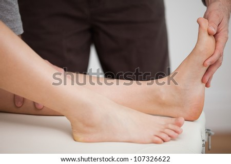 Physiotherapist manipulating the foot of a patient in a room - stock photo