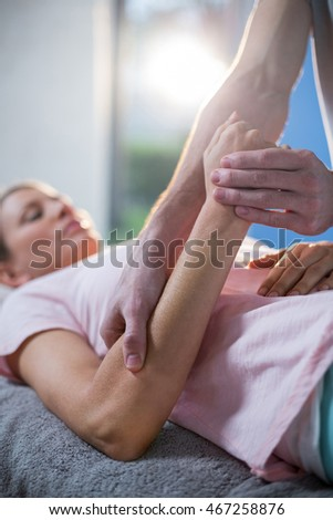 Physiotherapist massaging hand of a female patient in the clinic