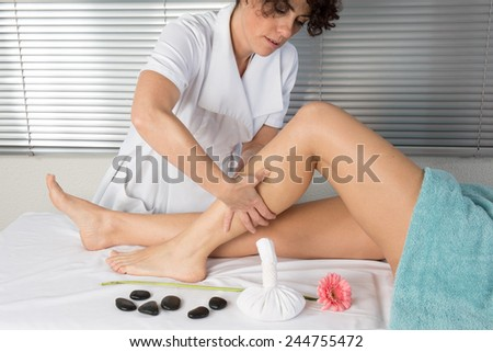 Physiotherapist massaging the calves of a woman - stock photo