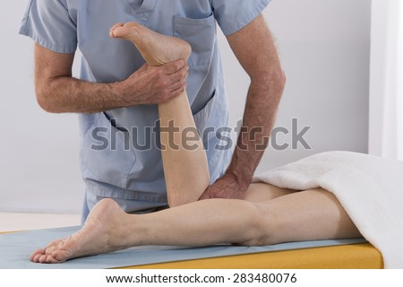 Physiotherapist stretching his patients leg in medical office