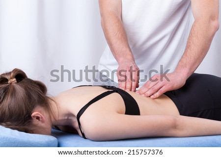 Physiotherapist touching tense muscle of the back - stock photo