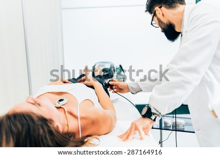 physiotherapist uses ultrasound treatment on muscles - stock photo
