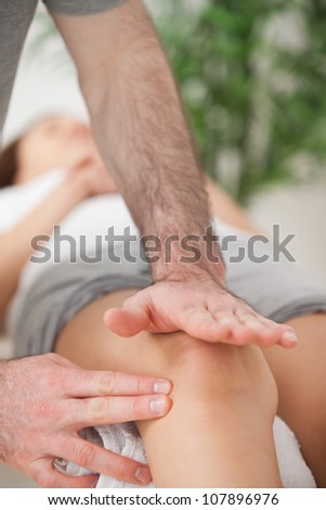 Physiotherapist using his hand palm to massage a knee indoors - stock photo
