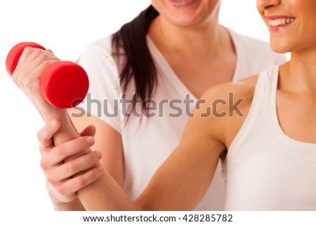 Physiotherapy - therapist doing arm  exercises with dumbbells for improving arm strenght and coordination  with a patient to recover  after injury - stock photo