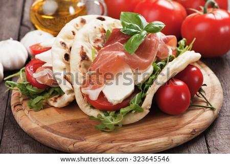 Piadina Romagnola, Italian Flatbread Sandwich with Prosciutto, mozzarella cheese, tomato and rocket salad - stock photo