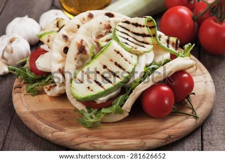 Piadina romagnola, italian flatbread sandwich with rocket salad, mozzarella cheese and grilled zucchini - stock photo
