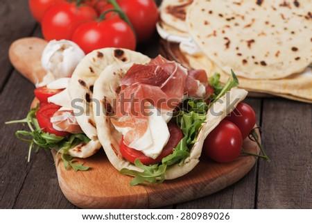 Piadina romagnola, italian flatbread sandwich with rocket salad, mozzarella cheese and prosciutto - stock photo
