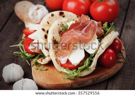 Piadina romagnola, italian flatbread sandwich wth prosciutto and mozzarella cheese - stock photo