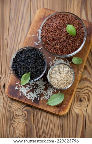 Pialats with rice kernels of different types on a chopping board - stock photo