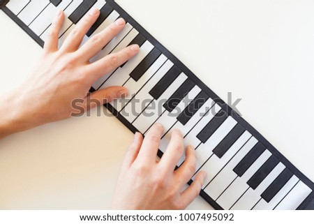 Pianist playing piano keyboard with both hands, piano learning concept, music education and music professionals.
