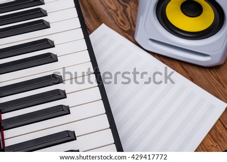 piano, blank music sheet and audio speaker - stock photo
