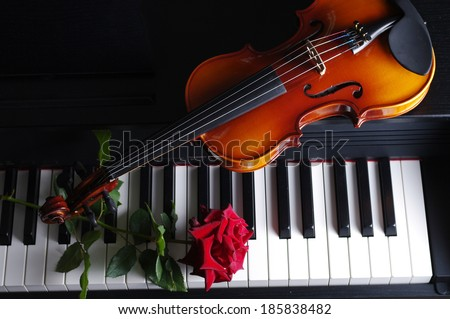Piano keyboard, violin and red rose