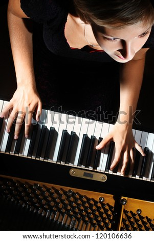 Piano music playing pianist musician. Musical instrument grand piano with beautiful woman performer. Focus is on the hands with instrument - stock photo