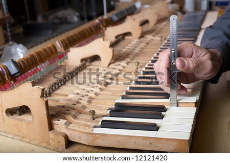 Piano technician at work checking key, DOF focus on hand - stock photo