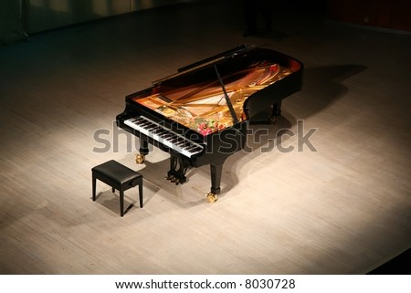 piano with  bouquet of flowers on scene in  concert hall - stock photo