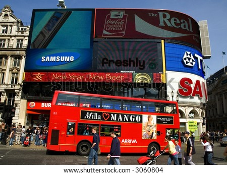 Piccadilly Circus in the spring with red bus in foreground - stock photo