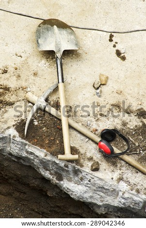 pick, shovel and  protective ear muffs to repair the sidewalks for construction mason men workers at  street city  - stock photo