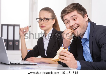 Picking teeth. Businessman picking teeth while sitting near his coworker - stock photo