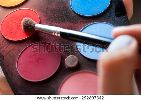 Picking the red color from the eyeshadow palette - stock photo