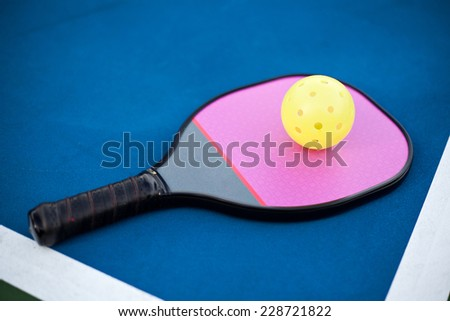 Pickleball paddle and ball on the court.  - stock photo