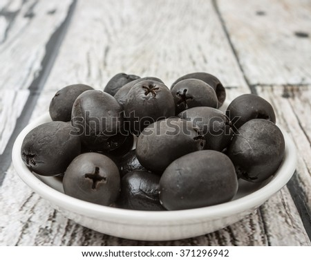 Pickled black olives fruit in white bowl over wooden background - stock photo